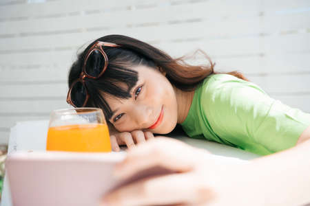 Young asian woman traveler wearing green shirt taking selfie with orange juice. 写真素材