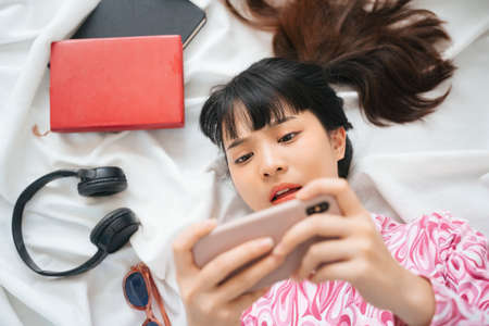 Top view - Young asian woman in pink shirt playing game with smartphone on bed.