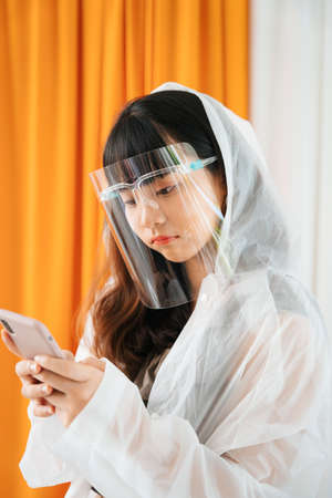 Young asian woman wearing white raincoat and face shield using smartphone.