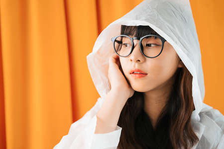 Fashion portrait of young asian woman wearing white raincoat and eyeglasses over orange curtain background. 写真素材