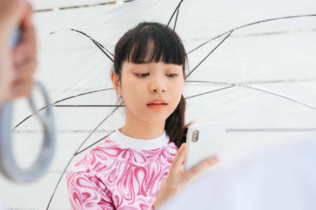 Young asian woman in pink shirt holding transparent umbrella and talking on the phone. Boyfriend waiting for her finish the phone call.