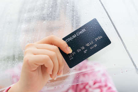 Hand of traveler woman in pink shirt holding credit card and umbrella. Shopping in rainy season concept.