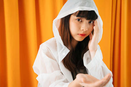 Close up portrait - Young asian woman wearing white raincoat on orange curtain background. 写真素材