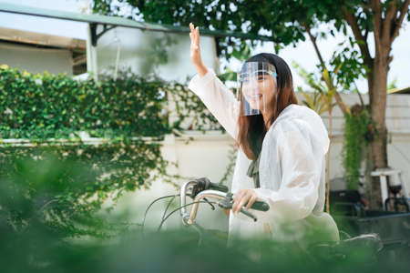 Young asian woman wearing white raincoat and face shield say hi to friend on bicycle. 写真素材