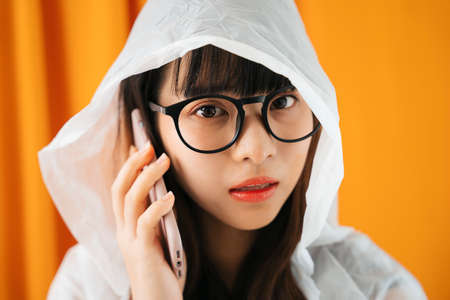Close up portrait of young asian woman wearing white raincoat and eyeglasses talking on the phone on orange curtain background.