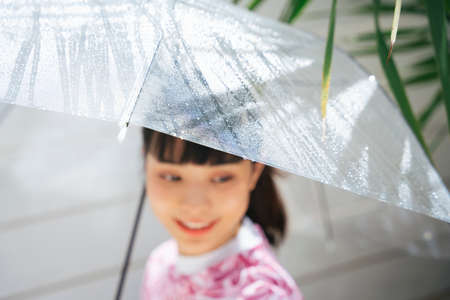 Young asian woman in pink shirt holding transparent umbrella in sunny day.