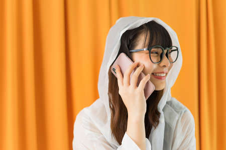 Side view - Young asian woman wearing white raincoat and eyeglasses talking on the phone on orange curtain background.