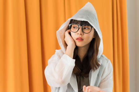 Young asian woman wearing white raincoat and eyeglasses on orange curtain background. 写真素材
