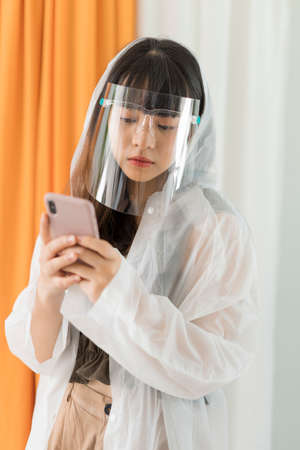 Young asian woman wearing white raincoat and face shield holding smartphone.