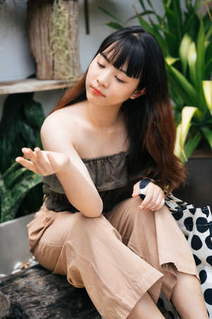 Young asian woman traveler sitting and touching the rain drop with hand at yard.