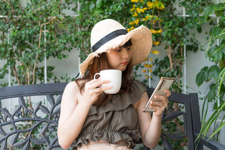 Young asian woman wearing hat using smartphone and holding a cup of coffee.