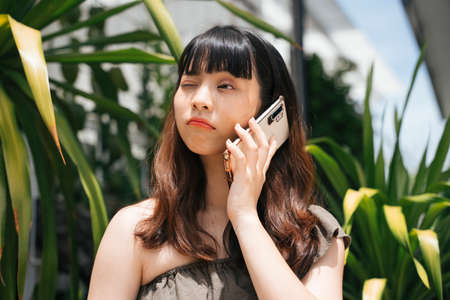 Young asian woman talking on smartphone having problem with boyfriend. 写真素材