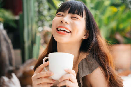 Cheerful young asian woman holding a cup of coffee at yard. Laughing expression.