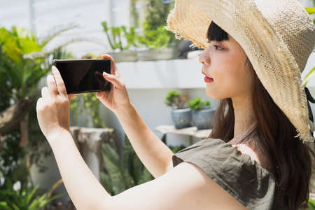 Young asian woman wearing hat holding smartphone at yard.