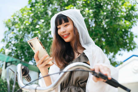 Young asian woman wearing white raincoat using smartphone on bicycle at park.