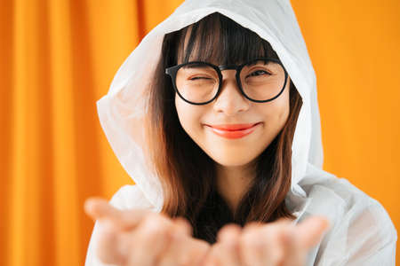Young asian woman wearing white raincoat and eyeglasses showing two hands for putting products. Wink expression.