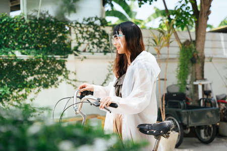 Young asian woman wearing white raincoat and face shield riding bicycle at park outdoors. 写真素材
