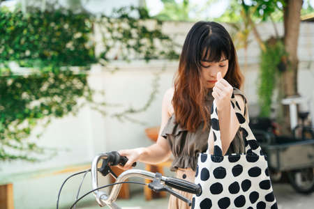 Young asian woman riding bicycle and looking at stuff inside shopping cloth bag. 写真素材