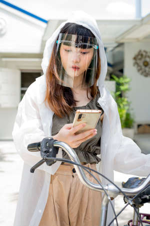 Young asian woman wearing white raincoat and face shield using smartphone on bicycle outdoors.