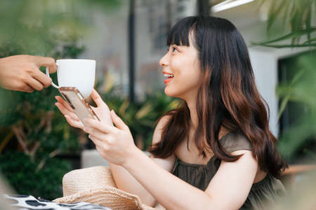 Side view - Young asian woman ordering coffee in dessert cafe outdoors.