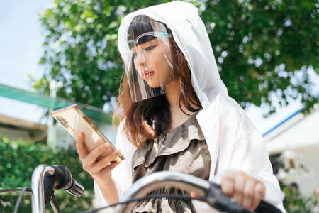 Young asian woman wearing white raincoat and face shield using smartphone on bicycle at park. 写真素材