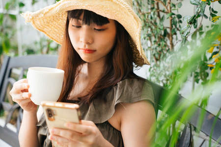Young asian woman wearing hat drinking coffee and using smartphone at yard. 写真素材