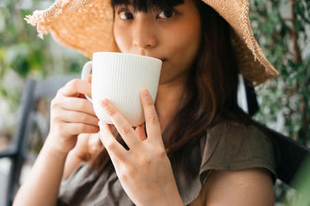 Close up - Young asian woman traveler wearing straw hat enjoy drinking coffee outdoors.