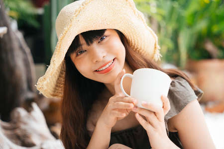 Young asian woman wearing hat holding a cup of coffee at yard outdoors.