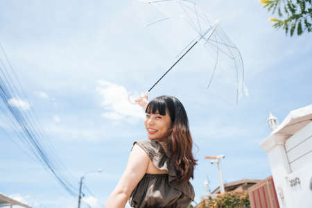 Young asian woman traveler holding transparent umbrella outdoors in sunny day.