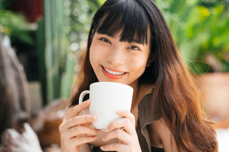 Cheerful young asian woman holding a cup of coffee at yard.