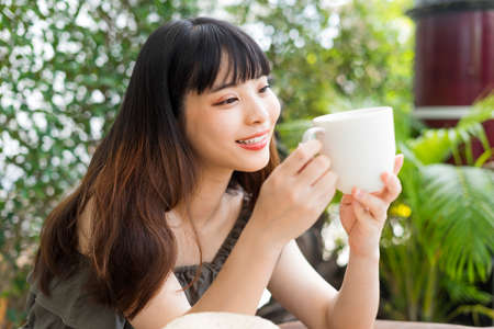 Young asian woman holding a cup of coffee outdoors at yard.
