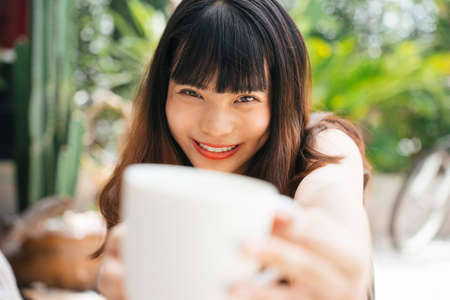 Close up portrait of young asian woman holding coffee cup with two hands close to camera. 写真素材