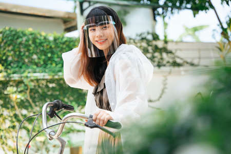 Young asian woman wearing white raincoat and face shield on bicycle at park outdoors.
