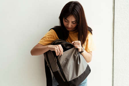 Cute girl in yellow t-shirt finding something in her backpack.