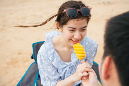 Beautiful asian woman eating piece of pineapple from her boyfriend hand.