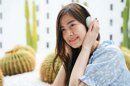 Beautiful asian woman enjoy listen to music with wireless headphone in cactus farm.