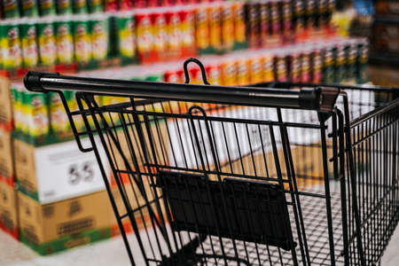 Supermarket aisle with empty black shopping cart. Reklamní fotografie
