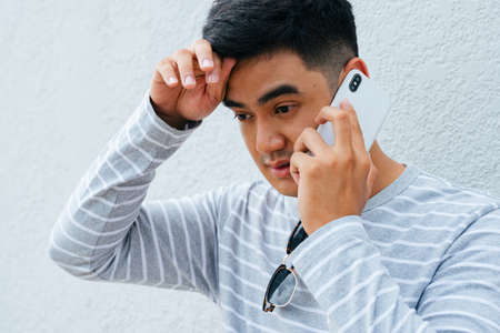 Upset asian man talking on the phone with concern looking. Banque d'images