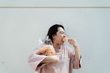 Long hair fat woman eat rice craker with wide mouth in front of white wall.