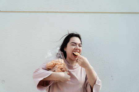 Long hair fat woman eat rice craker with wide mouth.