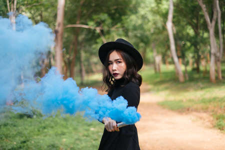 A black dress witch playing blue smoke torches in the forest. Stockfoto