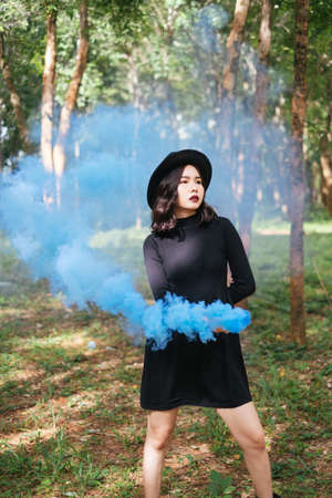 A black dress witch playing blue smoke torches in the forest.