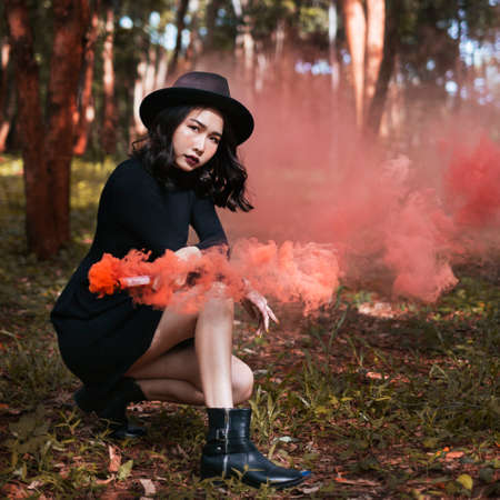 A black dress witch playing orange smoke torches in the forest.