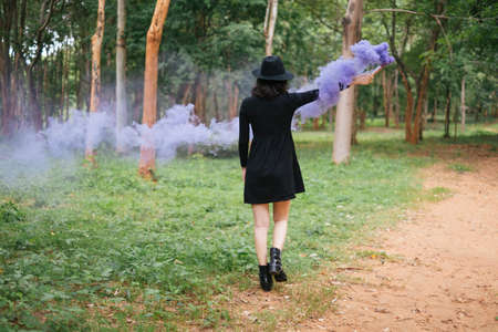 A black dress witch playing purple smoke torches in the forest.