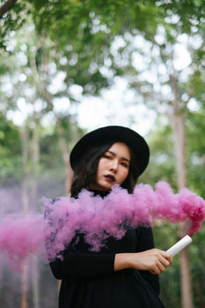 A black dress witch playing pink smoke torches in the forest.