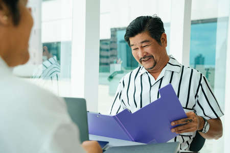 Adult asian businessman working with partner together in office room. Stock Photo