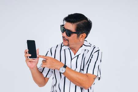 Portrait of hipster old elderly senior man in white collar shirt wear sunglasses showing smartphone screen.