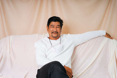 Fashion portrait of cool old elderly senior man in white shirt sittin on a couch.