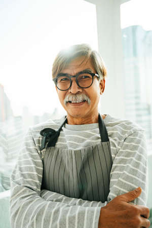 Portrait of old elderly senior waiter with eyeglasses in restaurant.