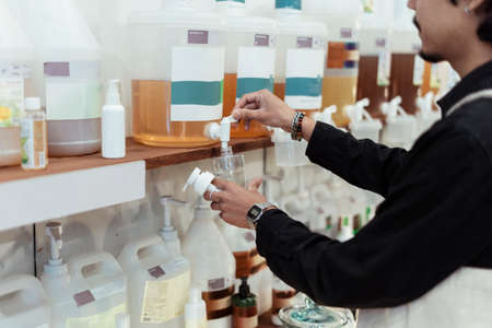 Cropped image of black hair man using dispencer in eco shop.